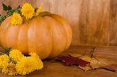 Orange Pumpkin With Yellow Flowers And Maple Leaves Against A Wooden Background (selective Focus On  poster