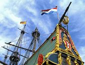 Flags waving above an ancient tall ship
