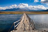 Shabby wooden bridge over a river with distant mountain range in background, Altai Mountains, Wester poster