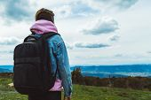 Tourist Traveler With Black Backpack On Background Mountain, Hiker Looks Up At Blue Sky Clouds, Girl poster