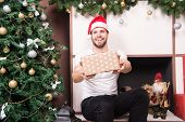 Happy Man Give Present Box At Christmas Tree And Fireplace. Gift Giving, Holiday Greeting. Boxing Da poster