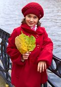 Little girl with autumn yellow leaves. Outdoor.