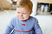 Cute Little Sad Baby Girl Crying. Hungry Or Tired Child Sitting Indoors And Having Tears poster