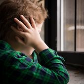 Close Up Of Kid Boy Standing Behind The Window In Sad Mood. Sad Teenager Looking In The Window And C poster