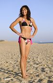 A happy forties woman on beach wearing bikini