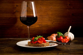 image of red wine  - photo of delicious bruschetta appetizer with red wine glass on wooden table - JPG
