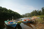 a flotilla of fishing boats line up on the river banks after returning from sea.