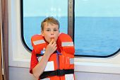 Boy dressed in life jacket blows whistle and stands near window in cabin of ship