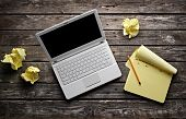 stock photo of stagnation  - Laptop with blank notepad and pencil with sheets of crumpled paper on old wooden table - JPG