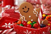 Fun image of smiling gingerbread man with peppermint stick in holiday snowflake dish with colorful c