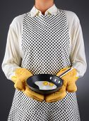 Closeup of a homemaker in an apron and oven mitts holding a pan with two fried eggs. Horizontal format over a light to dark background. Woman is unrecognizable. Shallow depth of field.