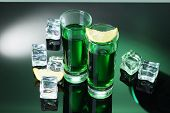 Two glasses of absinthe, lemon and ice on green background