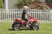 pic of four-wheeler  - A boy riding a four wheeler in motion - JPG