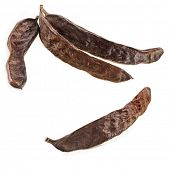 Carob pods on a white background