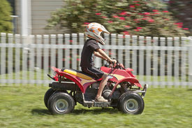 stock photo of four-wheelers  - A boy riding a four wheeler in motion - JPG