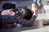 LHASA, TIBET-OCTOBER 08: A Tibetan female Buddhist pilgrim is praying in full ground prostration in front of the holy Jokhang Monastery on October 08, 2012 in Lhasa, Tibet.