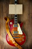 Red sunburst solid body electric guitar, with blank old paper on the neck for your message.