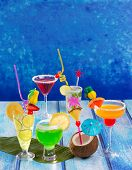 Colorful varied tropical Cocktails in tropical blue wood with coconut mojito pepermint margarita