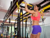 Crossfit fitness toes to bar woman pull-ups 2 bars with TRX foot assistant