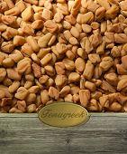 Fenugreek seeds  on Rustic wooden frame with golden label