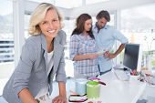 picture of paint pot  - Attractive designer looking at the camera while a couple is choosing colours - JPG