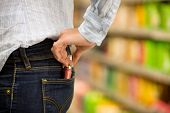 stock photo of shoplifting  - Theft of a young woman in a supermarket - JPG
