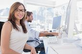 stock photo of mannequin  - Pretty designer smiling at the camera as her colleague works behind her - JPG