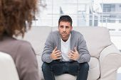 stock photo of upset  - Man telling therapist his problems sitting on the couch - JPG
