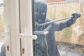 Burglar in garden opening the door with a crowbar