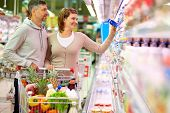 Image of happy couple with cart choosing products in supermarket