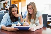stock photo of canteen  - Students watching something shocking on tablet in canteen in college - JPG
