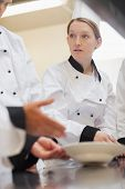 Trainee chef listening to teacher in culinary school