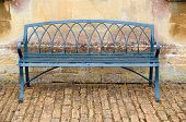 foto of cobblestone  - Empty iron antique bench on cobblestones against Bath stone - JPG