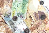 Qatari riyals currency bills and coins as a background