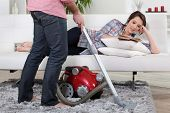 stock photo of suction  - Man using vacuum cleaner - JPG