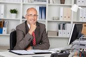 Businessman With Hand On Chin Sitting At Desk