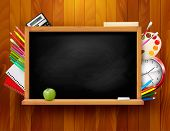 Blackboard with school supplies on wooden background. Raster version of vector.