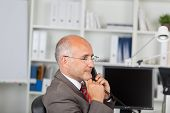 Thoughtful Businessman With Hand On Chin Using Landline Phone