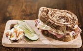 reuben sandwich with kosher dill pickle and coleslaw on wood plank