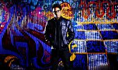 image of swag  - urban man in front of graffiti wall wide shot - JPG