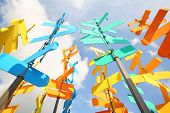 Set of multi-colored vanes and signs on background of blue sky with clouds.