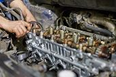 Hands of auto-mechanic, who repairs car engine