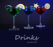 Alcoholic cocktails in martini glasses on dark blue background