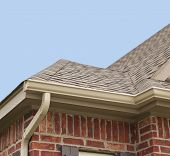 stock photo of downspouts  - House roof gutters and downspout on the corner of a house - JPG