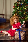 Red-haired Little Girl sitting On The Floor In Front Of Christmas Tree and unwrapping gift box