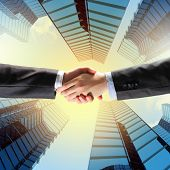 Close up image of hand shake against skyscrapers