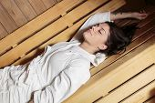 foto of sauna woman  - Young woman resting on a wooden bench in the sauna - JPG