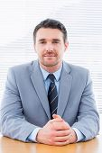 foto of half-dressed  - Portrait of a smiling confident young businessman sitting at office desk - JPG
