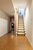 foto of basement  - Stairway to finished basement in home interior with wood paneling and cork flooring - JPG