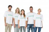 Group portrait of happy volunteers standing over white background